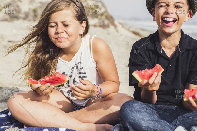 Siblings laugh while eating watermelon on the beach