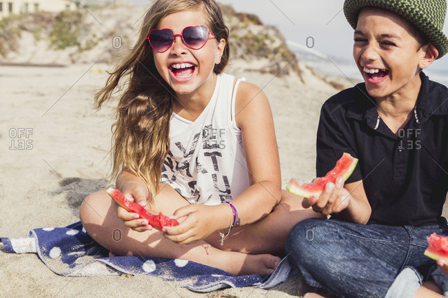 Children laugh while eating watermelon on the beach