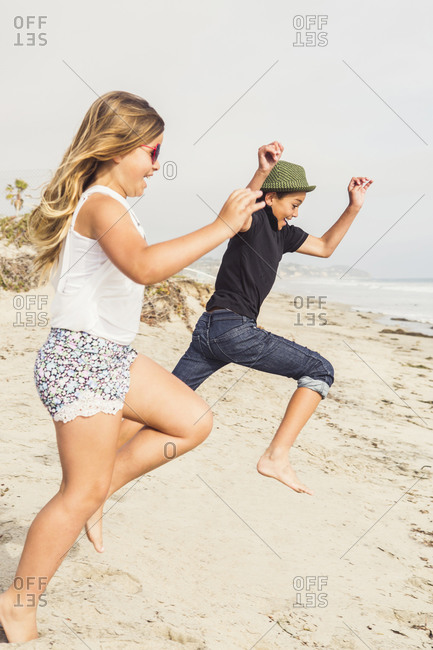Two children jump towards the beach