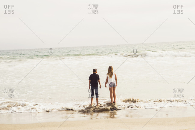 Two children stand on a rock on the surf