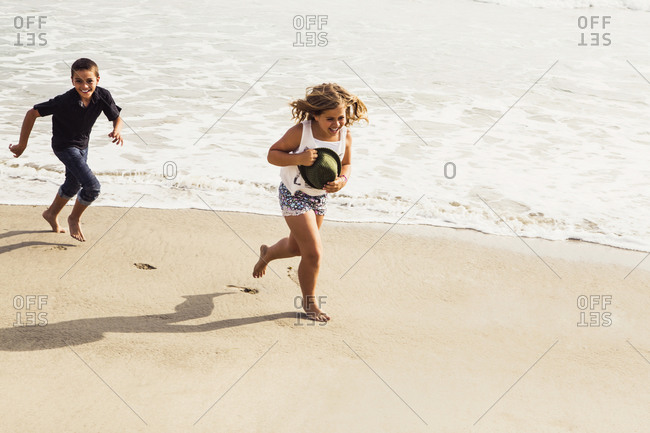 A young boy chases his sister at the beach