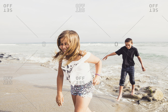 Two children laugh together at the beach
