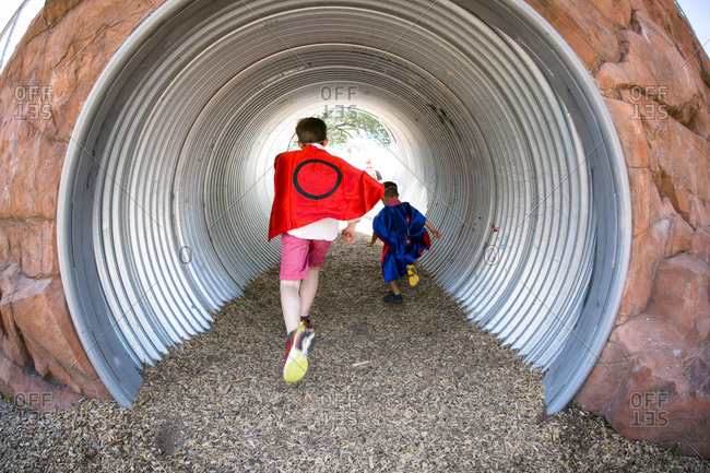 Costumed boys run through a drainage tunnel