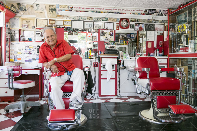 Albuquerque, New Mexico, USA - June 25, 2015: Martin Pena sits in the barber shop he has owned for decades