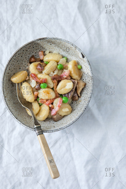 Fried gnocchi with bacon, wild mushrooms and peas