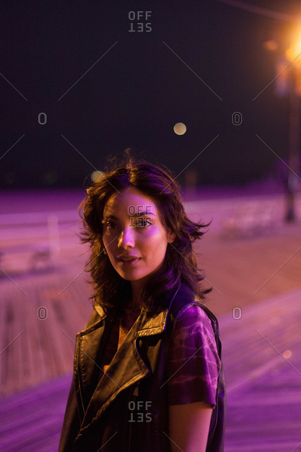 Portrait of a hip young woman on boardwalk at night