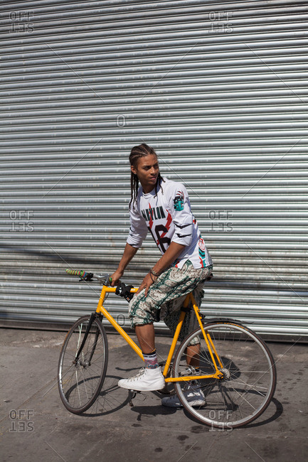 Young man with dreadlocks on bike in city