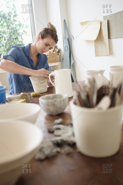 Young woman making pottery in studio