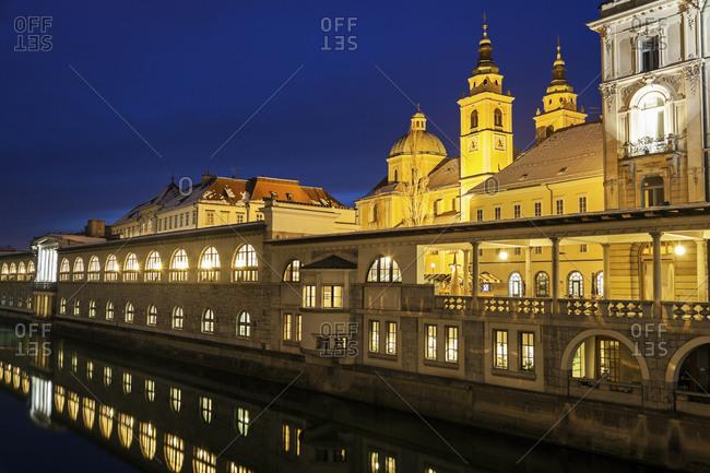 Illuminated waterfront with Saint Nicholas Cathedral, Ljubljana