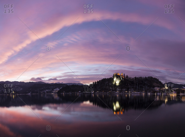 Clouds over Lake Bled and illuminated Church of the Assumption