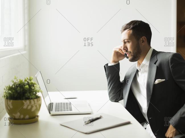Young man sitting at desk and looking at laptop
