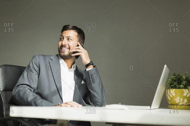 Young man sitting at desk and talking on phone