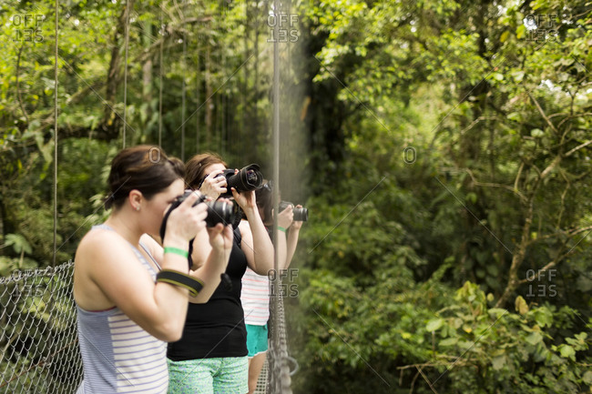 Young women photographing in forest