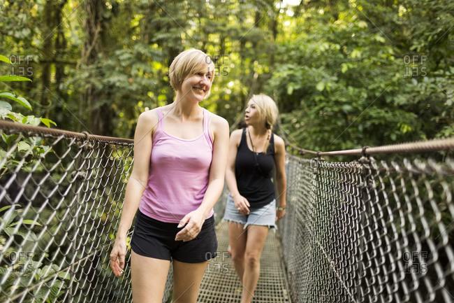 Young women walking on footbridge in forest