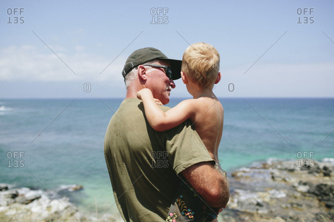 Senior man holding young grandson at oceanfront