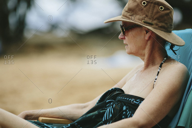 Senior woman in hat and sarong sitting in beach chair