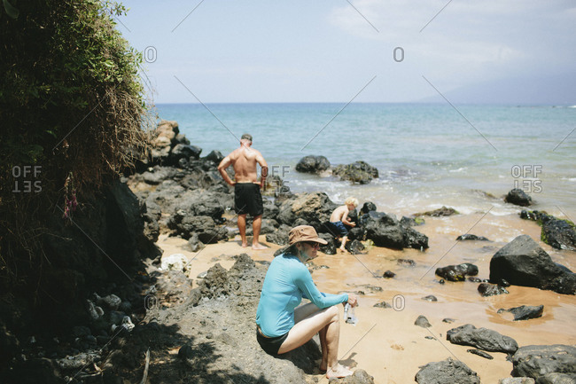Grandparents explore a rocky beach with grandson