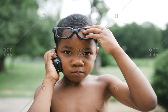 Little boy on cell phone lifting his glasses