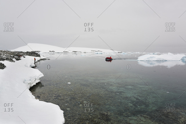 Group of people in a rubber boat moving towards the shore in the Antarctic ocean past an ice floe