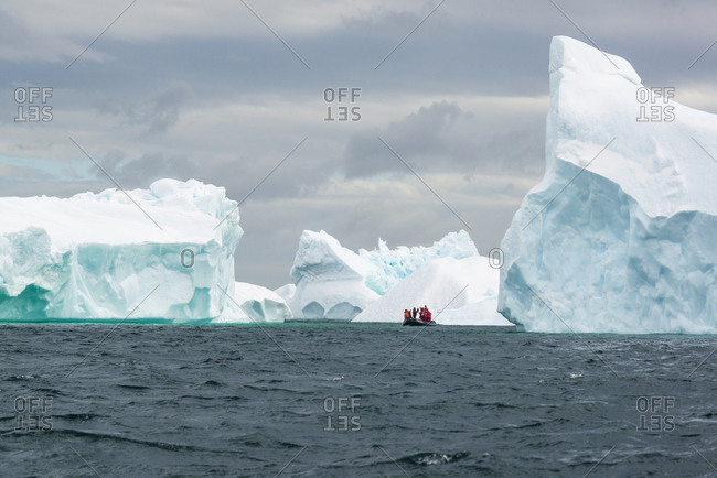 Group of people crossing the ocean in the Antarctic in a rubber boat with icebergs in the background