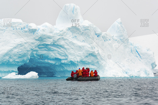 Tour group crossing the ocean in the Antarctic in a rubber boat with icebergs in the background
