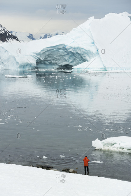 Man standing on the snow-covered shore in Antarctica icebergs and mountains in the background