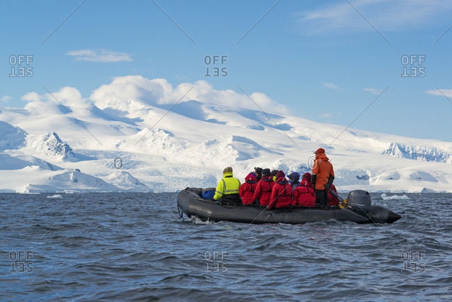 Group of people crossing the ocean in the Antarctic in a rubber boat with snow-covered mountains in the background