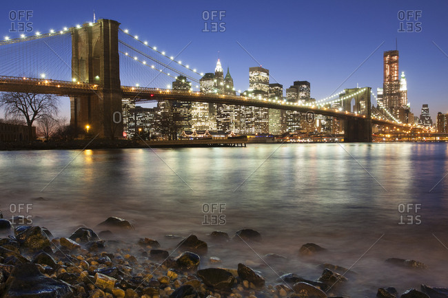 Night view towards Manhattan from Brooklyn with the Brooklyn Bridge spanning the East River