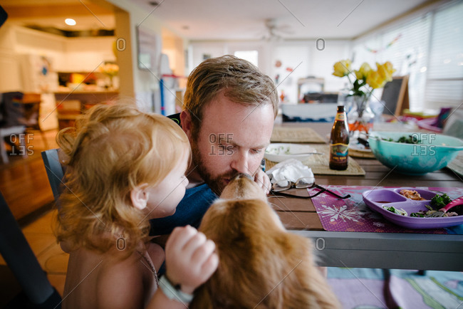 Father and daughter playing with pet dog