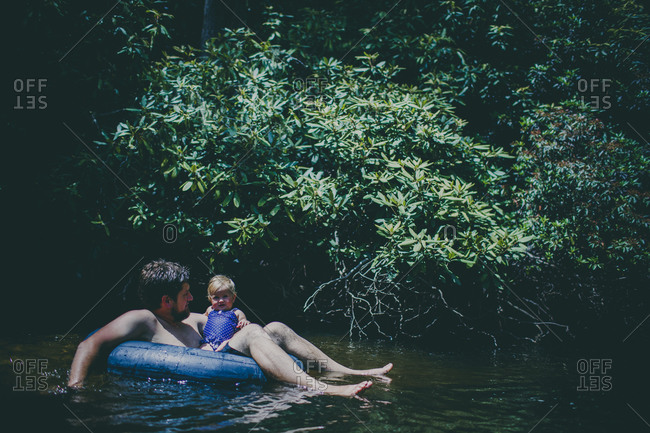 Father and daughter floating on a tube in a stream
