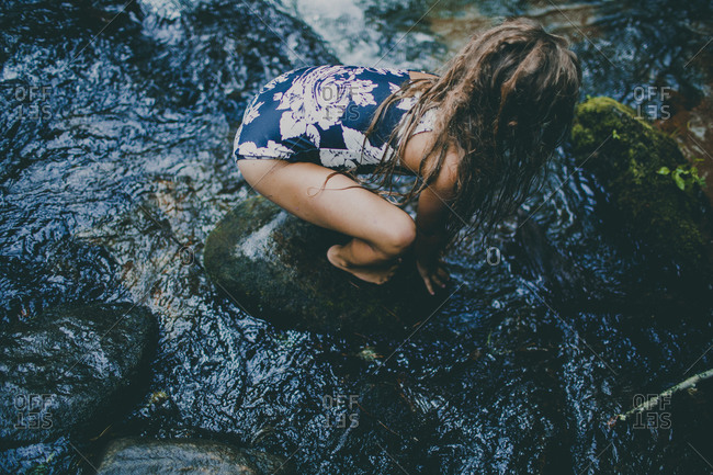 Girl cautiously stands on wet rocks