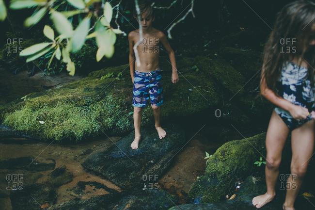 Children cautiously walking on mossy rocks