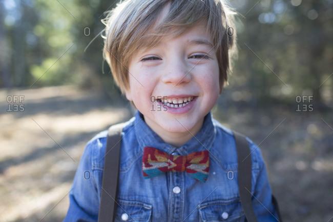 A boy in a denim shirt and a bowtie