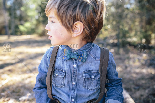 A boy in a denim shirt, bowtie, and suspenders