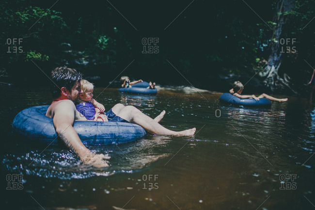 Father and children floating on tubes in a stream