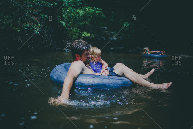 Father and child floating on a tube in a stream