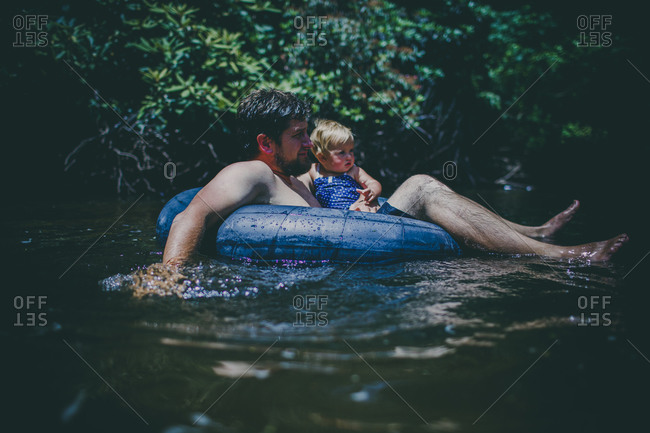 Father and child floating on a tube