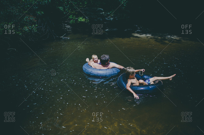 Dad and his kids floating on tubes in a stream