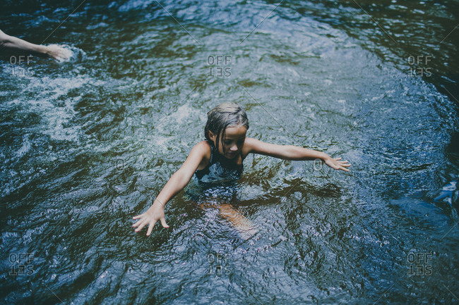 Girl swimming in a stream