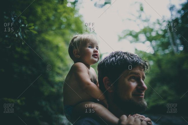 Happy toddler sitting on her father's shoulders