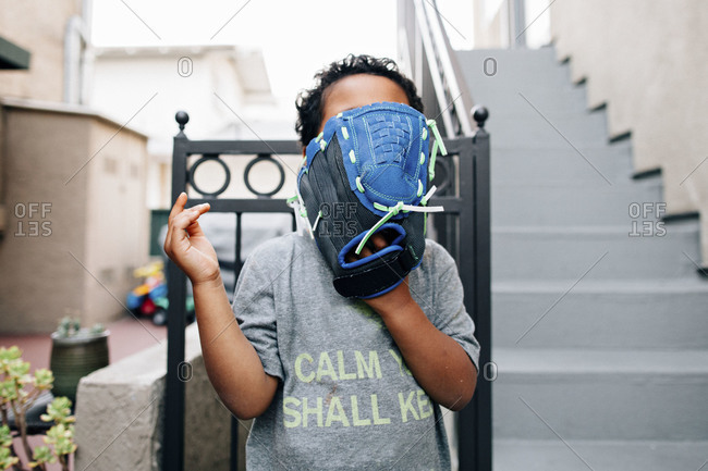 Little boy covering his face with baseball mitt