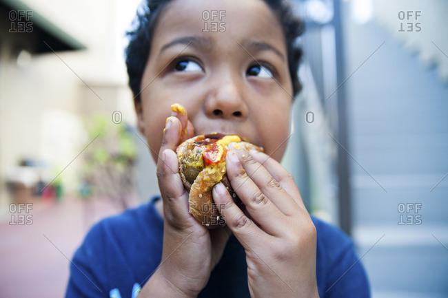 Portrait of little boy eating a hamburger