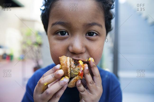 Portrait of little boy taking bite of hamburger