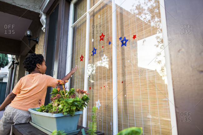 Little boy looking at window with patriotic decorations