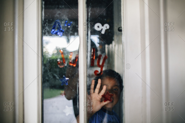 Boy touching window with Fourth of July stickers