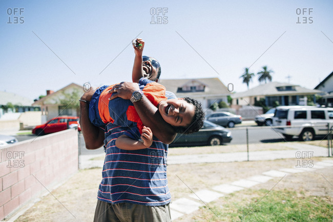 Boy laughing in man's arms in yard