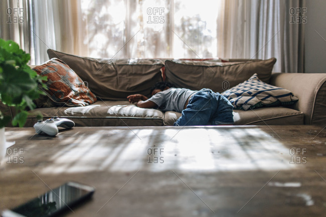 Little boy asleep sprawled over couch