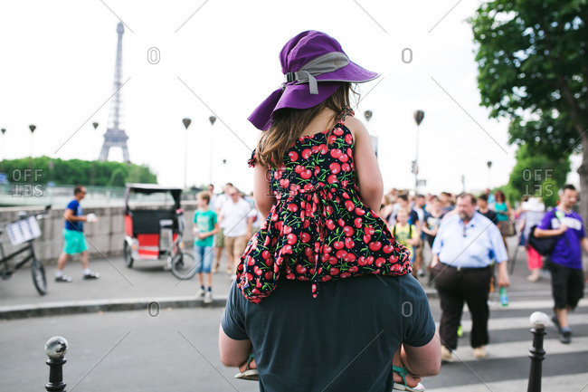 Dad carrying girl on shoulders in Parisian street