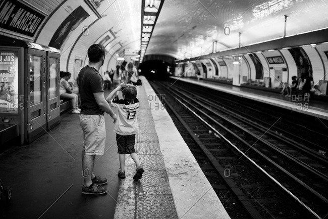 Paris, France - July 4, 2015: Man and boy waiting in Parisian subway station