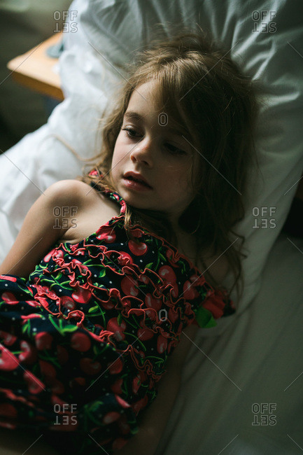Little girl lying on hotel bed staring off